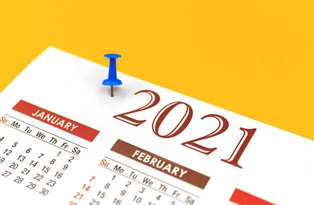 Calendário 2021 com alfinete, conceito de organizador e planejador, close-up e foto de foco seletivo