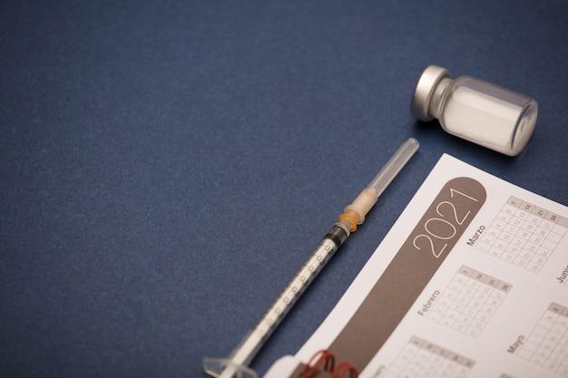 Calendário 2021 com seringa e recipiente de vacina, superfície azul