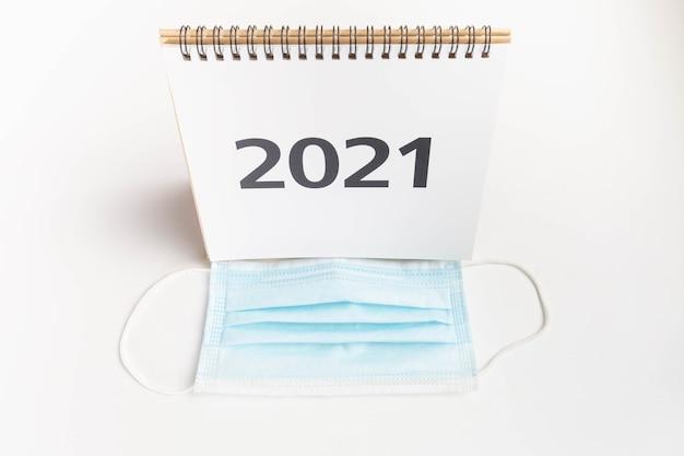 Calendário 2021 na frente da máscara facial em fundo branco