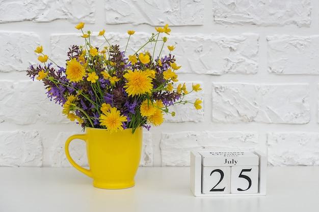 Calendário 25 de julho e copo amarelo com flores coloridas brilhantes contra a parede de tijolos brancos.
