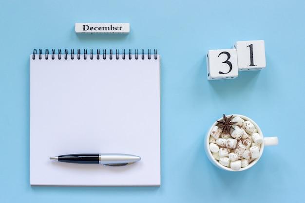 Calendário 31 de dezembro xícara de cacau e marshmallow, bloco de notas aberto vazio