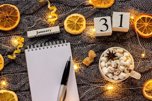 Calendário 31 de janeiro xícara de chocolate e bloco de notas aberto vazio