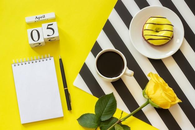 Calendário 5 de abril. xícara de café, donut amarelo e rosa, bloco de notas aberto vazio
