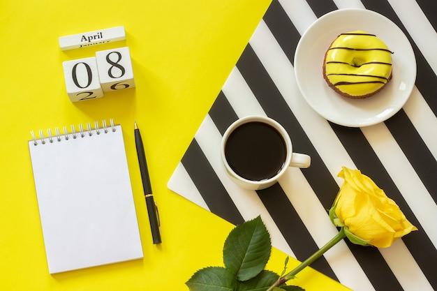 Calendário 8 de abril. xícara de café, rosquinha, rosa, o bloco de notas. local de trabalho elegante conceito