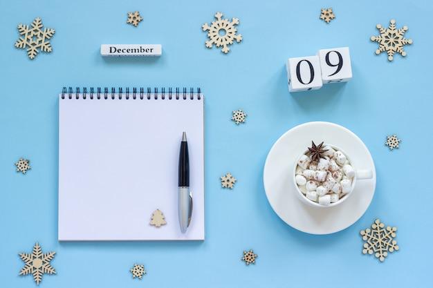 Calendário 9 de dezembro xícara de cacau e marshmallow, bloco de notas aberto vazio