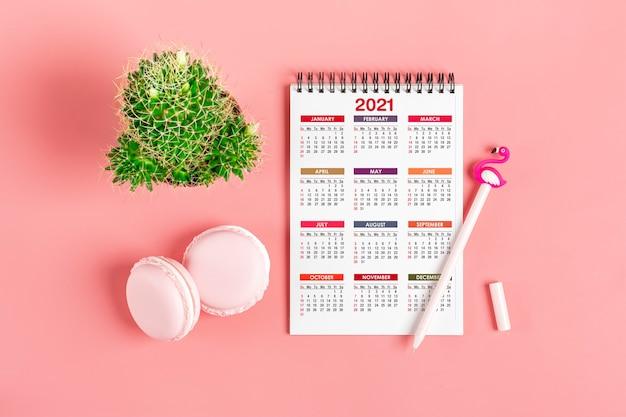 Calendário aberto de janeiro de 2021, velas, caneta, doces, suculentas na mesa rosa