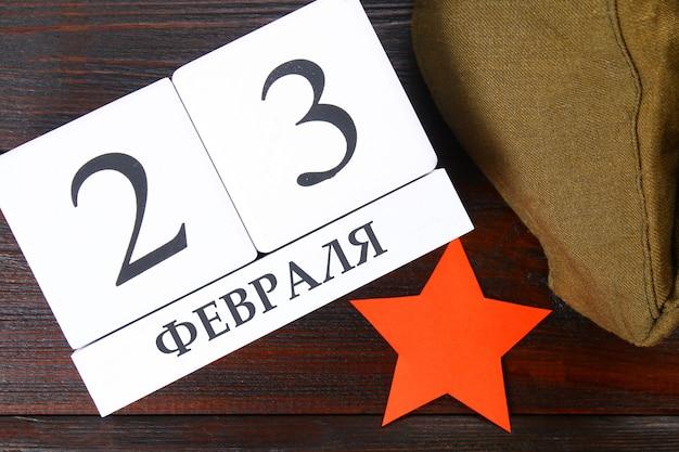 Calendário branco com texto em russo: 23 de fevereiro. feriado é o dia do defensor da pátria.