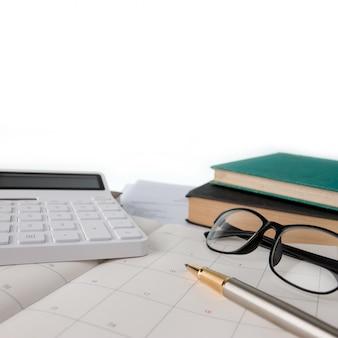 Calendário, calculadora, óculos, caneta e cadernos