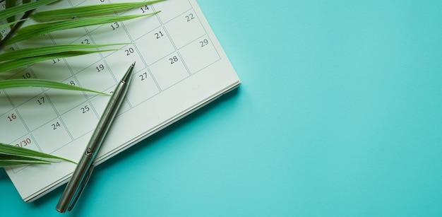 Calendário com caneta e folhas tropicais em fundo azul para férias de verão