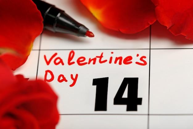 Calendário com data de 14 de fevereiro e pétalas de flores rosa. conceito de dia dos namorados