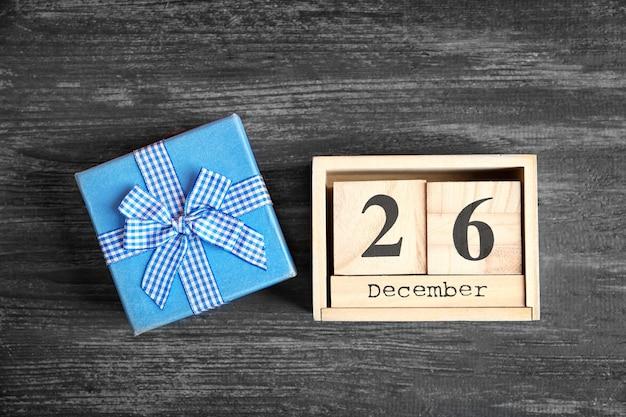 Calendário com data e caixa de presente em fundo de madeira. conceito de natal