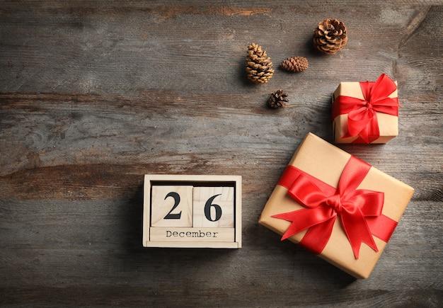Calendário com data e caixas de presente em fundo de madeira. conceito de natal