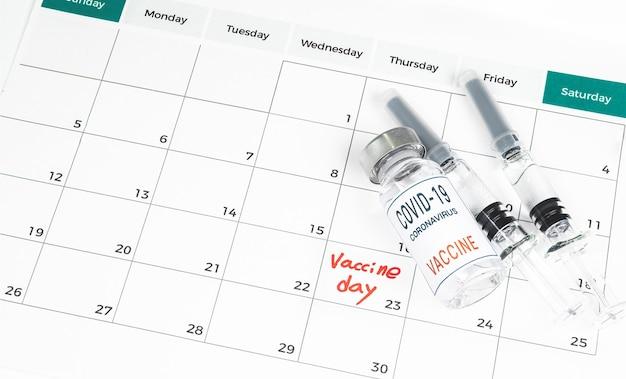 Calendário com datas de vacinação, uma vacina covid-19 e um conceito médico com uma seringa.