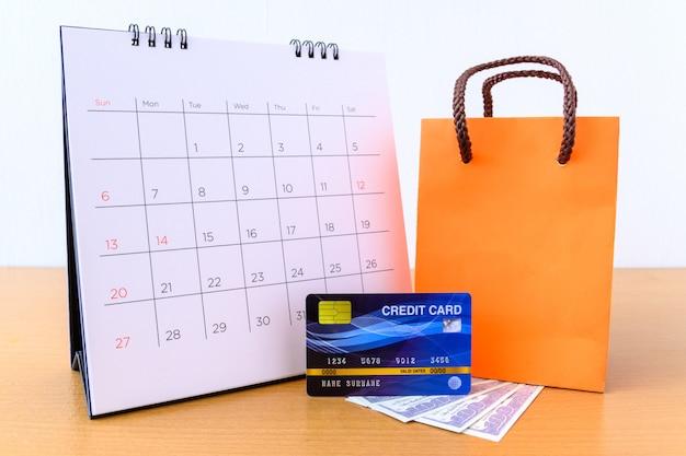 Calendário com dias e cartão de crédito e saco de papel laranja na mesa de madeira. conceito de compras