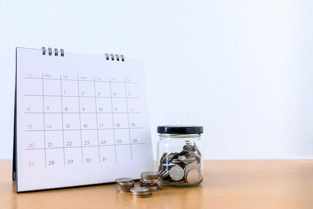 Calendário com dias e moedas no pote na mesa de madeira