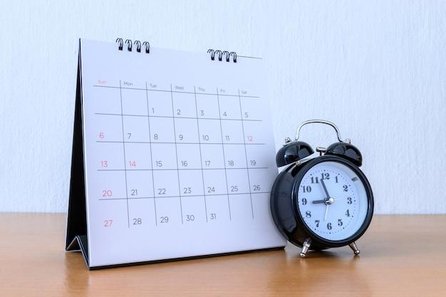 Calendário com dias e relógio na mesa de madeira