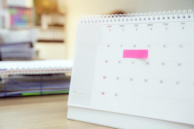 Calendário com mensagem de nota de papel na mesa de escritório para planejador de eventos.