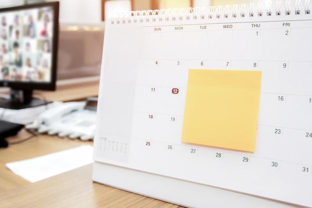 Calendário com nota de papel na mesa de escritório para planejador de eventos.