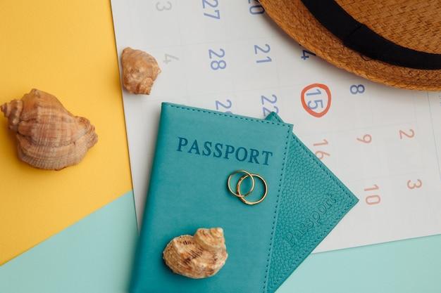 Calendário com passaportes, chapéu e anéis em superfície colorida. lua de mel, conceito de casamento. data da viagem