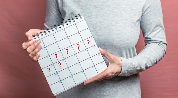Calendário com pontos de interrogação nas mãos de uma mulher. atraso da menstruação.