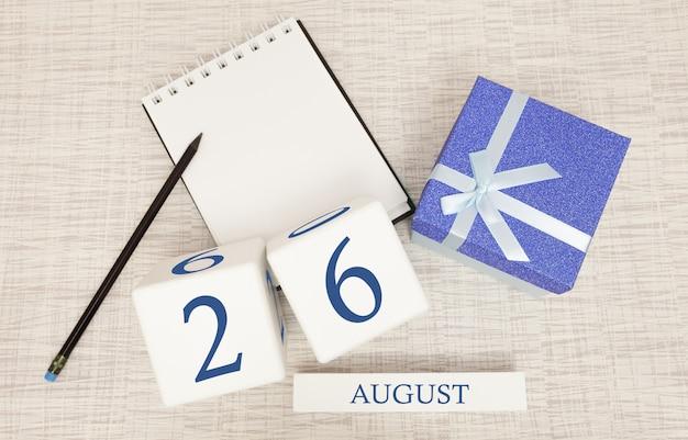 Calendário com texto azul na moda e números para 26 de agosto e um presente em uma caixa.
