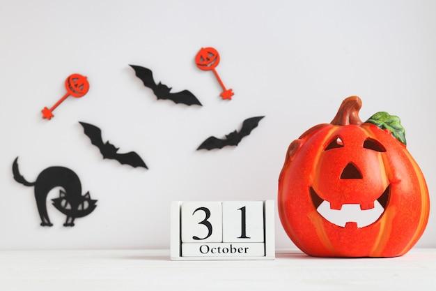 Calendário datado de 31 de outubro jackolatern gato preto e morcegos na mesa branca cartão de halloween