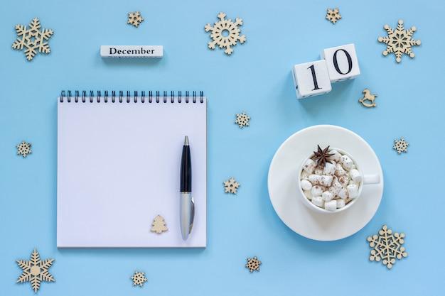 Calendário de 10 de dezembro copo de cacau e marshmallow, bloco de notas aberto vazio