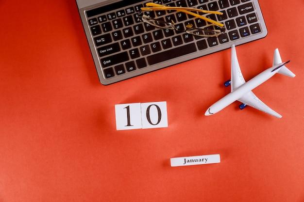 Calendário de 10 de janeiro com acessórios na mesa de escritório de espaço de trabalho de negócios no teclado do computador, avião, óculos fundo vermelho