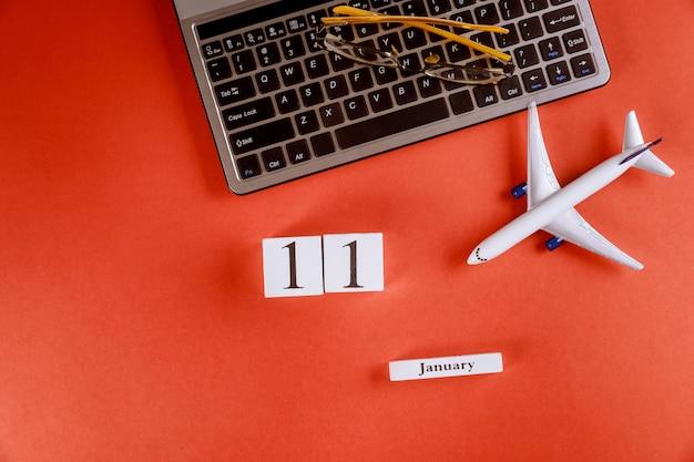 Calendário de 11 de janeiro com acessórios na mesa de escritório de espaço de trabalho de negócios no teclado do computador, avião, óculos fundo vermelho