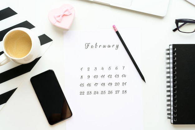 Calendário de 14 de fevereiro no espaço de trabalho com cartão de dia dos namorados com coração de presente rosa, xícara de café, flatlay