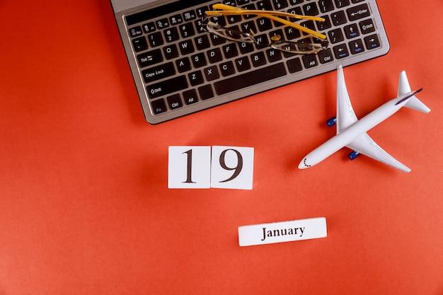 Calendário de 19 de janeiro com acessórios na mesa de escritório de espaço de trabalho de negócios no teclado do computador, avião, óculos fundo vermelho