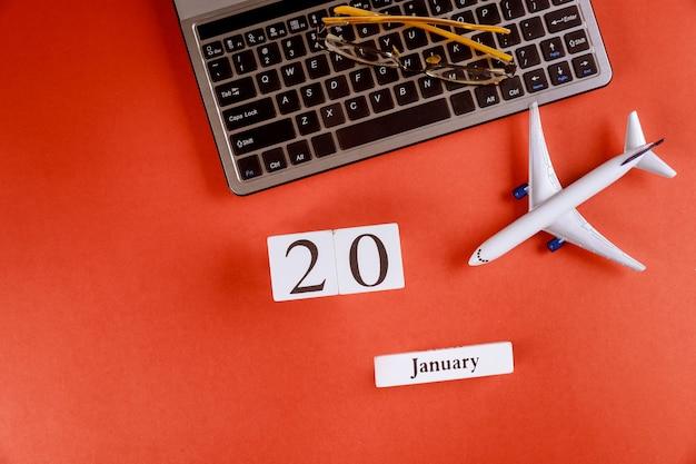 Calendário de 20 de janeiro com acessórios na mesa de escritório de espaço de trabalho de negócios no teclado do computador, avião, óculos fundo vermelho