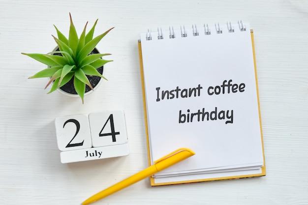 Calendário de 24 de julho em blocos de madeira - conceito de férias de aniversário de café instantâneo