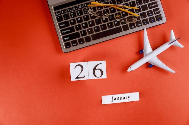 Calendário de 26 de janeiro com acessórios na mesa de escritório de espaço de trabalho de negócios no teclado do computador, avião, óculos fundo vermelho