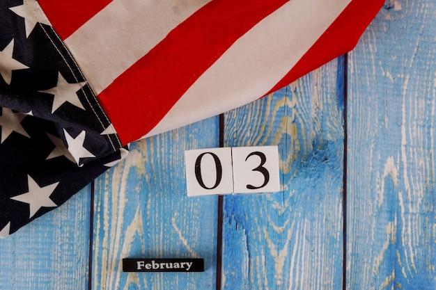 Calendário de 3 de fevereiro, maravilhosamente acenando estrelas e listrada bandeira americana na prancha de madeira velha.