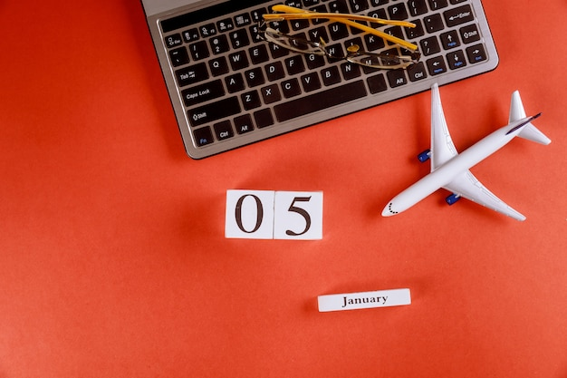 Calendário de 5 de janeiro com acessórios na mesa de escritório de espaço de trabalho de negócios no teclado do computador, avião, óculos fundo vermelho
