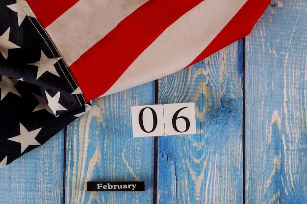 Calendário de 6 de fevereiro, maravilhosamente acenando estrelas e listrada bandeira americana na prancha de madeira velha.