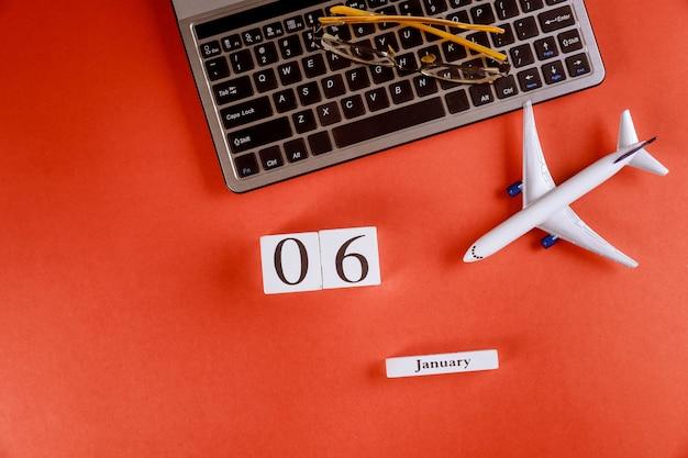 Calendário de 6 de janeiro com acessórios na mesa de escritório de espaço de trabalho de negócios no teclado do computador, avião, óculos fundo vermelho