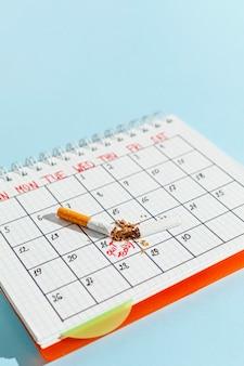 Calendário de alto ângulo com cigarro
