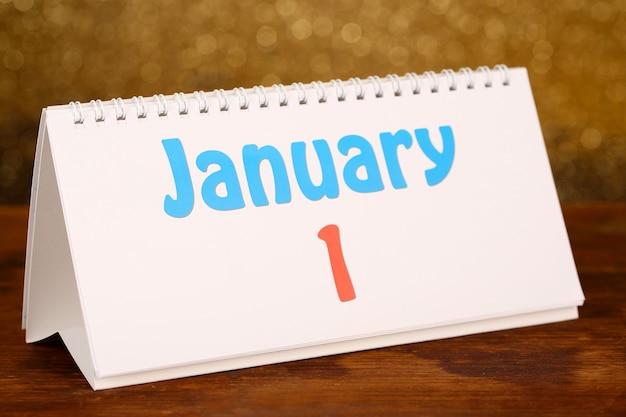 Calendário de ano novo na mesa de madeira, sobre fundo dourado brilhante