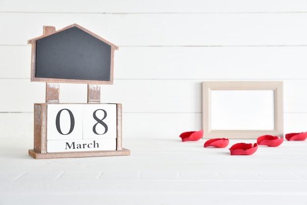 Calendário de bloco de madeira de texto de 8 de março com moldura de imagem e pétala de rosas vermelhas