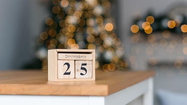 Calendário de blocos de madeira com a data de dezembro no fundo do bokeh das luzes de natal