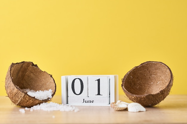 Calendário de blocos de madeira com data 1 de junho e coco com sal marinho em fundo amarelo. conceito de férias de verão