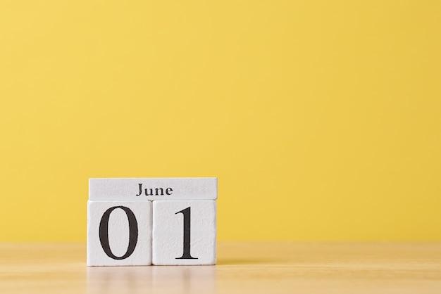 Calendário de blocos de madeira com data de 1º de maio em fundo amarelo