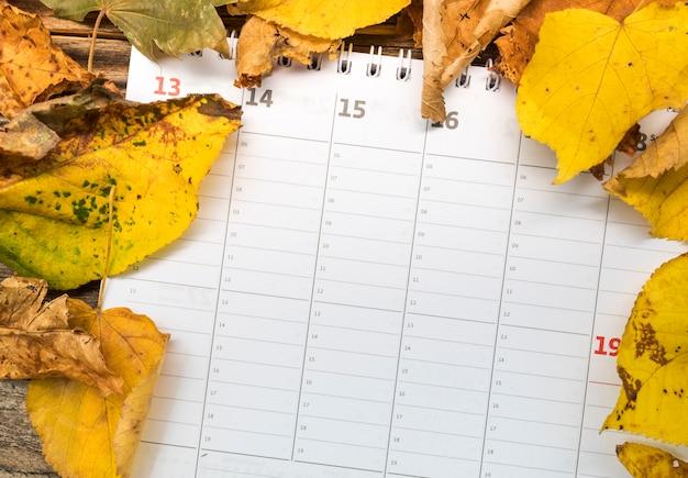Calendário de configuração plana com arranjo de folhas douradas
