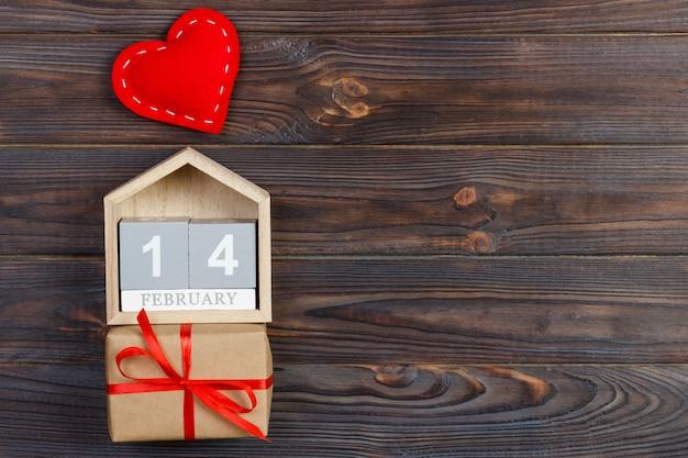 Calendário de cubo com coração vermelho e caixa de presente na mesa de madeira com espaço de cópia. 14 de fevereiro de conceito