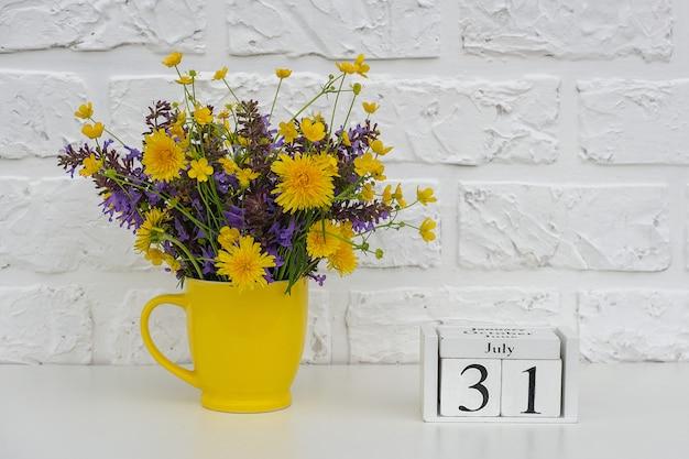 Calendário de cubos 31 de julho e copo amarelo com flores coloridas brilhantes contra a parede de tijolos brancos