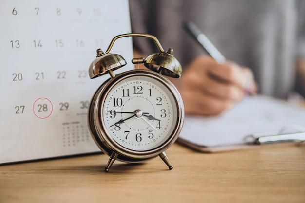 Calendário de data de vencimento e mulher de negócios trabalhando