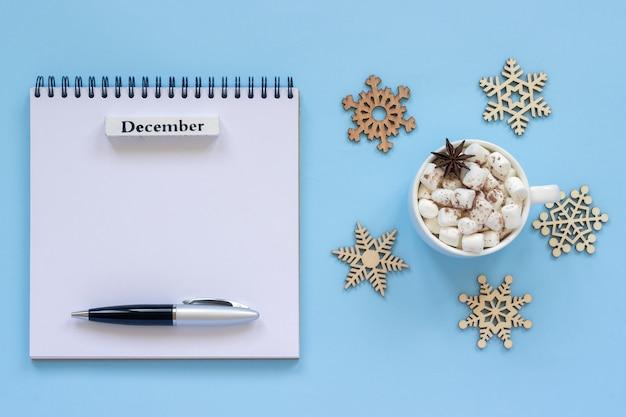 Calendário de dezembro e a xícara de chocolate com marshmallow, bloco de notas aberto vazio
