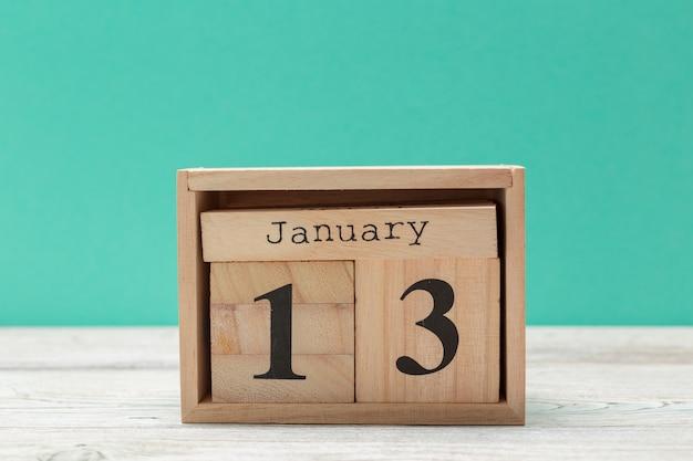 Calendário de forma de cubo de madeira para 13 de janeiro na mesa de madeira